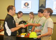 Ryan Akers (left), an assistant Extension professor in the Mississippi State University School of Human Sciences, helps 4-H members examine items in a disaster preparedness backpack. Madison Crawford (second from left) and Leigh Anne Walley, both of Greene County, joined Caleb Walley and Bo Henderson, both of Wayne County, in the workshop on June 1 at the 2017 State 4-H Congress in Starkville, Mississippi. (Photo by MSU Extension Service/Linda Breazeale)