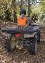 A rider wears camouflage, an orange vest and a helmet in the woods with a rifle case on the back of the ATV.