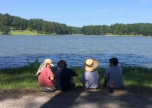 Four buddies enjoy a break overlooking Choctaw Lake in the Tombigbee National Forest near Ackerman, Mississippi. (Photo by MSU Extension Service/Evan O'Donnell)