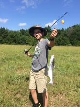 A teenage boy proudly holds up a catfish on his fishing line.