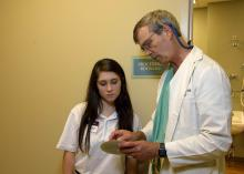 A teenage girl looks on as a doctor explains a chart in his hands.