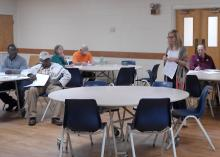 Blonde-haired woman with glasses in a large room speaking to a group of farmers.