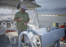 A man stands on a boat and checks a large roll of fishing line.