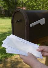 A pair of hands holds a stack of mail taken from a mailbox.