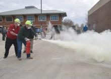 Two men wearing hard hats and masks activate a fire extinguisher as MyPI training participants watch.