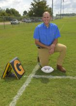 A man in a blue shirt kneels on a chalk-lined football field beside a goal line marker. A white Mississippi State football rests on the ground beside his knee.