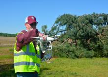 Man wearing a reflective safety vest looks at a white drone he is holding at shoulder height. A toppled pine tree and empty agricultural field are in the background.