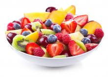 A white bowl of mixed chopped fresh fruits and berries on white background.
