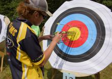 A 4-H'er wearing sunglasses tallies arrows in a colorful paper archery target.