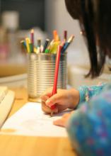 A child uses a colored pencil to write on a sheet of paper.