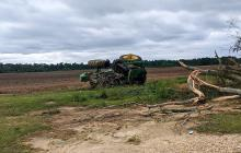 Green tractor flipped on its side in a field.