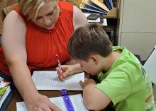 A woman looks on while a young boy writes on a piece of paper.