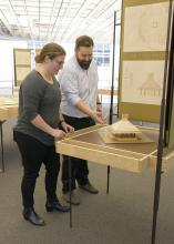 A woman and a man examine a small, wooden model of a building.
