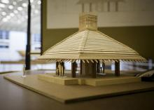 A wooden model of a building rests on a table in an exhibit hall.