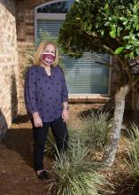 A woman wearing a mask stands in the landscape outside a house.