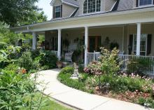 A sidewalk leads to a front porch through a shrub-filled landscape.