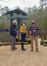 Three people stand in front of a pavilion while cutting a ceremonial ribbon.