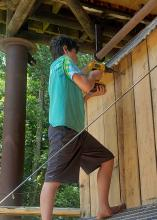A boy uses a drill to work on a wooden structure.