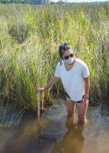 Girl wading knee-deep in water measuring its depth with a yardstick