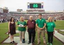 Five people pose for a photo on a football field.