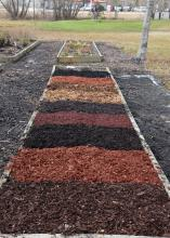 A rectangular garden bed with different colors of mulch divided into squares.