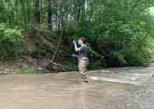 Woman in wading pants collects a water sample in a creek.