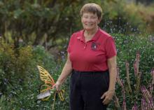 A woman holding a gardening tool stands in a green landscape.