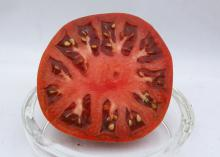 A sliced tomato sits in a glass dish.