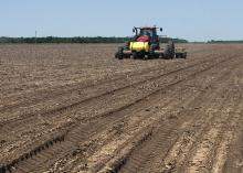 Clear skies have been rare sights as Mississippi farmers started planting their 2016 crops. This soybean planter is establishing a variety trial in a Sunflower County field on May 10, 2016. (MSU Extension Service photo/Greg Flint)