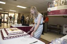 Meaghan Gordon, marketing coordinator at the Mississippi State University Office of Agricultural Communications, cuts the cake May 8, 2014 at the Bost Extension Center that commemorates the 100th anniversary of the Extension Service. Friends of the Extension Service gathered in similar events around the state to celebrate the anniversary. (Photo by MSU Public Affairs/Megan Bean)