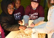 Third-graders from Houston Upper Elementary School, including, from left, Jamyrie Davenport, Sedrick Walker and R.J. Utz, pet a baby chicken held by a volunteer at the Mississippi State University Extension Service FARMtastic event at the Mississippi Horse Park near Starkville on Nov. 13, 2014. (Photo by MSU Ag Communications/Kevin Hudson)