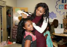 Korie Stallings, 8, gets her hair pinned by Mississippi State University senior Claudia Robinson of Jackson, Mississippi. Robinson and other School of Human Sciences students made dresses for girls in the Starkville Boys and Girls Club as part of an apparel design class service-learning project. Participants modeled new dresses in a fashion show on Dec. 5, 2015. (Photo by MSU Extension Service/Kat Lawrence)