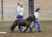 Cassie Brunson, coordinator of the Mississippi State University Extension Service Therapeutic Riding and Activity Center, runs beside Little Sam, led by Paige Davis Linley, 10, a participant in the first Therapeutic Riding Expo, held Tuesday night (April 14) at the Mississippi Horse Park near Starkville, Miss. (Photo by MSU Public Affairs/Megan Bean)