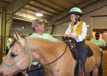 Volunteer Lantz Stewart of West Point offers advice to Eli Barlow before they enter the arena for the first Therapeutic Riding Expo at the Mississippi Horse Park on April 14, 2015. (Photo by MSU Ag Communications/Linda Breazeale)
