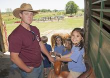 Mississippi State University animal and dairy science major Jacob McCarty of Summit, left, shows Starkville Academy student Abby Edwards how to sit properly in a saddle during Afternoon on the Farm May 1, 2015. The activities took place at the H.H. Leveck Animal Research Center at MSU, commonly called the South Farm, in Starkville. (Photo by MSU Extension Service/Kat Lawrence)