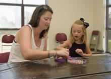 A parent's involvement can make any activity a learning experience. Jaden Claire Everett, 5, fashions a dog out of beads as her mother, Jana Carolyn Everett, assists. (Photo by MSU Ag Communications/Kevin Hudson)
