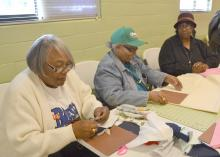 Annette Lockett, left, Thelma Washington and Mary Kohn, members of a newly formed Mississippi Homemaker Volunteers Club in Holmes County, cut out and sew quilt squares as part of a quilt-making project on Nov. 24, 2015. The group donated 67 lap quilts to residents at the Lexington Manor Senior Care facility. (Photo by MSU Ag Communications/Susan Collins-Smith)