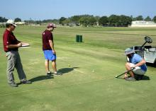 Mississippi State University Department of Plant and Soil Sciences senior research associate Wayne Philley, left, and MSU seniors Abram Diaz of D'Iberville and Aaron Tucker of Carthage measure how far a golf ball rolls over different varieties of bermudagrass at the R. R. Foil Plant Science Research Center Sept. 4, 2015. (Photo by MSU Ag Communications/Nathan Gregory)