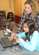 Khadeeja Baig enters information into the computer that will program her robot to turn in a circle as children's librarian Becky Bowen looks on. Baig is one of 15 children enrolled in the second session of a six-week robotics course at the Rebecca Baine Rigby Library in Madison. (Photo by MSU Extension Service/Susan Collins-Smith)