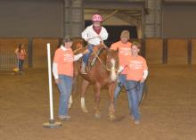 """Ji Ji Pridmore leads an """"equine therapist"""" named Fred around a pole, while Kylie Grace Robertson of Hamilton communicates her commands with the reins. Side walkers Fay Ray and Lantz Stewart assist on April 19, 2016, at the second annual Therapeutic Riding Expo at the Mississippi Horse Park, located south of the Mississippi State University campus. (Photo by MSU Extension Service/Linda Breazeale)"""