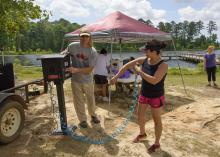 Jim McAdory, Mississippi State University Extension Service agent to the Mississippi Band of Choctaw Indians, shows Natasha Willis how to use the sunscreen dispenser provided by MSU Extension. The demonstration was part of a May 28 boating event in Neshoba County, Mississippi. (Photo by MSU Extension Service/Kevin Hudson)