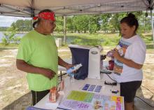 Ricky Willis learns about sun safety from Candy Jimmie at the May 28 boating event at Lake Pushmataha in Neshoba County, Mississippi. (Photo by MSU Extension Service/Kevin Hudson)