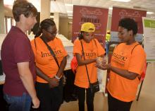 Union County Extension agent Gina Wills, left, watches as India Hamilton, Kaitlyn McGee and Ja'vonne Rich examine a newly hatched chick at the poultry booth on Oct. 5, 2016, at a career expo for eighth-graders in Tupelo, Mississippi. The three students, all from Armstrong Middle School in Starkville, Mississippi, were among 7,000 students taking part in the event sponsored by the CREATE Foundation Toyota Wellspring Education Fund and many other individuals, companies and civic organizations. (Photo by MSU E