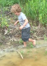 Getting dirty is half the fun for children exploring and playing in the great outdoors. Rain may drive families inside for a time, but they provide some great water features after the thunder and lightning have passed. (Photo by MSU Extension Service/Evan O'Donnell)