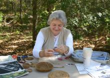 Judy Breland, Mississippi State University Extension Service agent in Stone County, demonstrates pine needle basket weaving at the 2015 Piney Woods Heritage Festival at the MSU Crosby Arboretum in Picayune, Mississippi. The 2016 festival is set for Nov. 18 and 19. (Photo by Mississippi State University Extension Service/Pat Drackett)