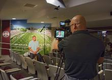 Brian Utley, video producer with MSU Extension's Agricultural Communications, focuses a camera on former MSU football quarterback Dak Prescott in July 2016. Prescott is the face of the 2017 Public Service Announcement campaign for the 70x2020 Colorectal Cancer Screening Initiative. (Photo by MSU Extension/Kevin Hudson)