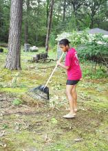 Andrea Brown, a 14-year-old Oktibbeha County 4-H member, rakes limbs and debris in the yard of a senior adult friend in the Bell Schoolhouse Community. Many Mississippians are depending on the help of friends and family to assist in cleaning up in the wake of Hurricane Katrina.