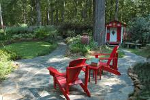 Red can be a difficult color to use in gardens, and the secret to its success sometimes lies in using it as an accent. The first thing that catches the eye in this outdoor room is the bright red Adirondack chairs. A short walk away is an idyllic children's play house of the same color. (Photo by Norman Winter)