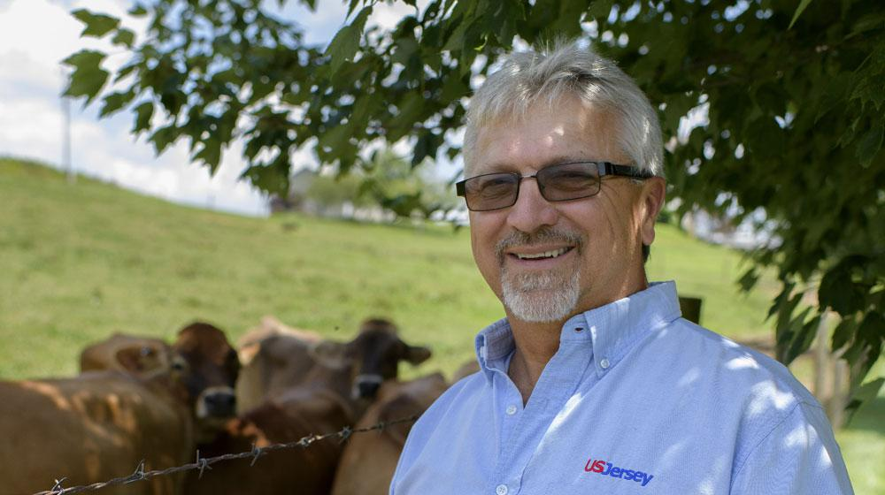 "A man wearing a light blue shirt with ""US Jersey"" above the chest pocket stands smiling in front of several cows."