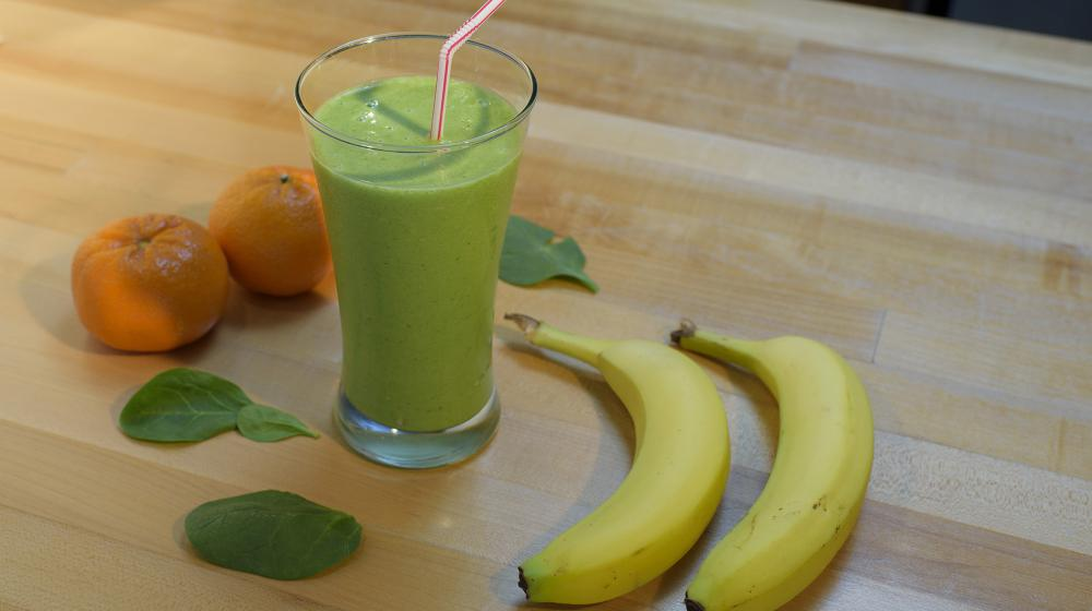 A green smoothie fills a tall clear drinking glass and has a red and white striped straw in it.